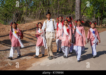 Daily lifestyle. Students and teacher go to lessons on a mountain road in the Himalayas. - Stock Photo