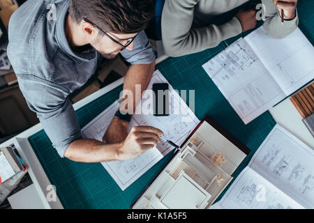 Top view of two male architects sitting in office and working on project. Creative people working on new architectural - Stock Photo