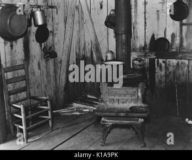 A modest kitchen belonging to a sharecropper, with a well-used wooden stove, a chair awaiting repairs against the - Stock Photo