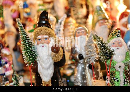 Close-up, hand-decorated European Father Christmas and Santa figurines/ornaments, holding Christmas tree at Old - Stock Photo