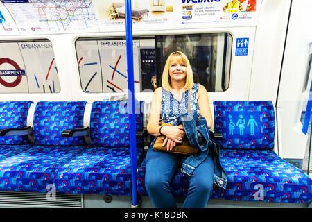 Woman on her own using London underground, Woman on her own using London tube train, Sat on London tube train, sitting - Stock Photo
