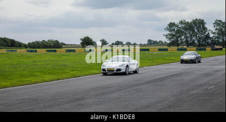 Porsche Cayman cars racing at Croft Motor Racing Circuit,North Yorkshire,England,UK - Stock Photo
