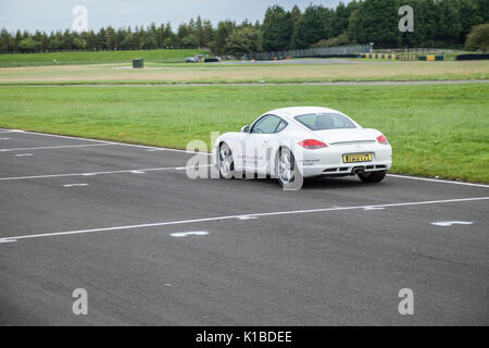 White Porsche car driving around Croft Motor Racing Circuit,North Yorkshire,England,UK - Stock Photo