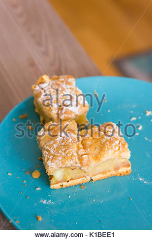 Three apple pie pieces with powder sugar on a blue plate in soft focus - Stock Photo