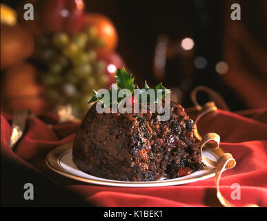 Traditional Christmas pudding on red tablecloth shallow focus - Stock Photo