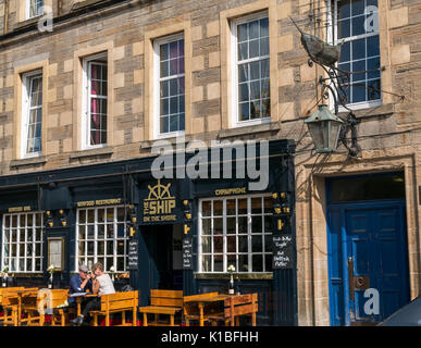 Leith restaurant, The Ship on the Shore, with Persevere ship model emblem on wall and couple sitting outside in - Stock Photo