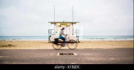 BOURNEMOUTH, UK - AUGUST 22, 2017: Cyclist Rides passed a Life Guard Station on Bournemouth Beach - Stock Photo