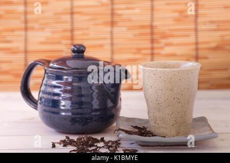 tea in ceramic teapot on wood table - Stock Photo
