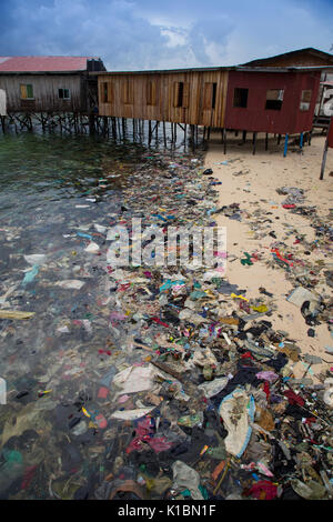 Plastic trash and other garbage covers a beach in front of budget dive resorts on Mabul Island, Borneo - Stock Photo