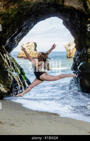 Dancer jumping in cave - Stock Photo