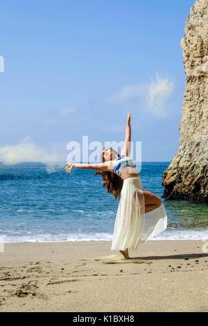 Dancer on Beach with yellow powder - Stock Photo