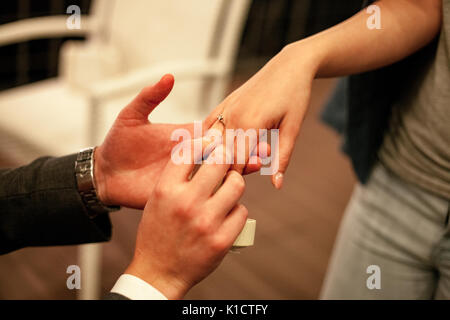 Man makes woman marriage proposal and puts on engagement ring with diamond on her finger. Close up. - Stock Photo