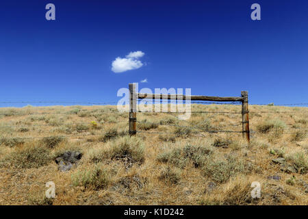 A single cloud hanging over a barbed wire fence in the middle of the desert in Utah. - Stock Photo