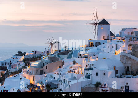 Townscape with windmills, dusk, Oia, Santorini, Cyclades, Greece - Stock Photo