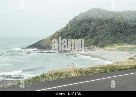 view from Oregon coast highway fog crested rocky wooded promontory sheltering small sand beach with a few beachcombers - Stock Photo
