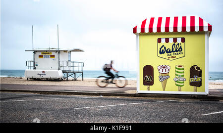 BOURNMOUTH, UK - AUGUST 22, 2017: Cyclist Rides passed a Life Guard Station towards a Walls Ice Cream Stand on Bournemouth - Stock Photo