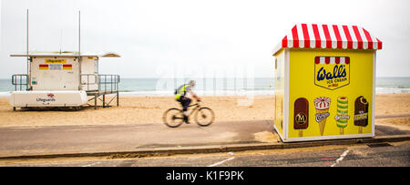 BOURNEMOUTH, UK - AUGUST 22, 2017: Cyclist Rides passed a Life Guard Station towards a Walls Ice Cream Stand on - Stock Photo
