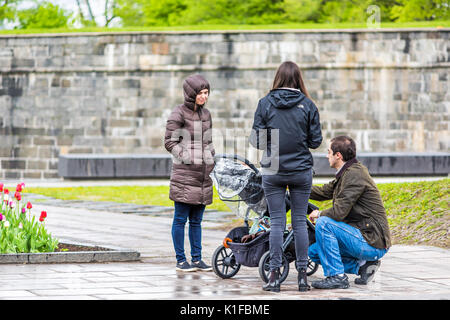 Quebec City, Canada - May 30, 2017: Family with stroller and child talking with friends in park during rainy day - Stock Photo