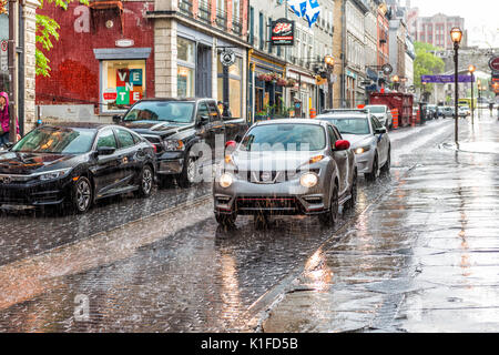 Quebec City, Canada - May 31, 2017: Old town street Saint-Jean during heavy rain with drops and wet road, car - Stock Photo