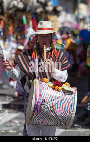 June 17, 2017 Pujili, Ecuador: man playing on flute and drum simultaneosly walking the  Corpus Christi parade - Stock Photo