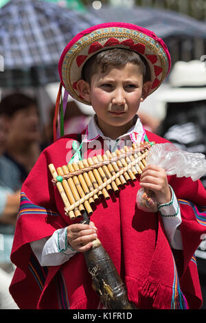 June 17, 2017 Pujili, Ecuador: young boy in traditional clothing at the Corpus Christi parade holding a pan flute - Stock Photo