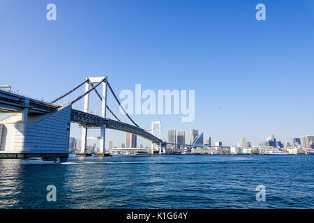 Tokyo, Japan - Jan 4, 2016. Rainbow Bridge with modern buildings background in Tokyo, Japan. View from tourist boat - Stock Photo