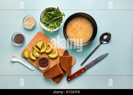 Dinner table. Vegetarian soup with mushrooms and toast with arugula, avocado, sesame and quino chia on the wooden - Stock Photo