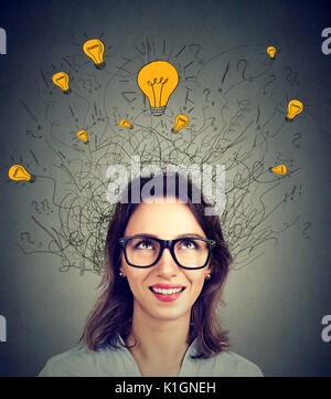 Young woman in glasses with many ideas light bulbs above head looking up isolated on gray wall background. Eureka - Stock Photo
