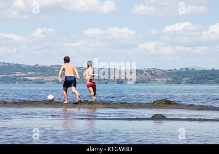 Summer time. Two little boys playing football on a sandy strip in the middle of the lake. - Stock Photo