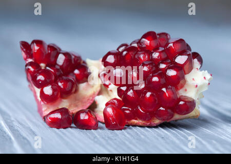 Pomegranate seeds. Part of pomegranate fruit. old gray wooden background. Macro view. (Soft focus). - Stock Photo