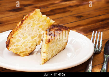 Spanish omelet on a white plate. The plate on the wooden table. Spanish omelette with potatoes and onion. Tortilla - Stock Photo