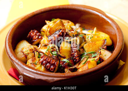 Pulpo a feira, octopus galician style. Octopus with fried potatoes in a clay plate. (soft focus) - Stock Photo