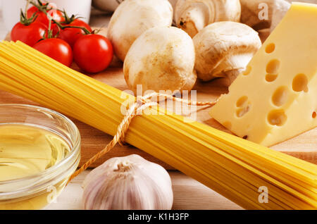 Pasta ingredients. Cherry-tomatoes, spaghetti pasta, garlic, cheese and mushrooms on a kitchen table - Stock Photo