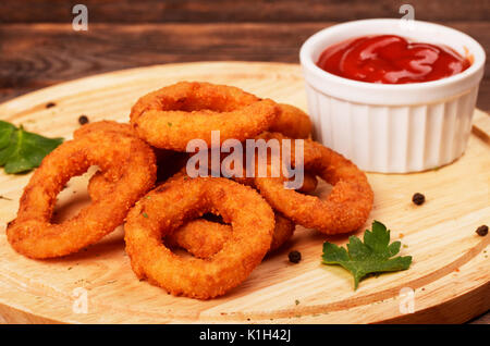 Homemade breaded crunchy fried onion rings with ketchup on cutting board - Stock Photo
