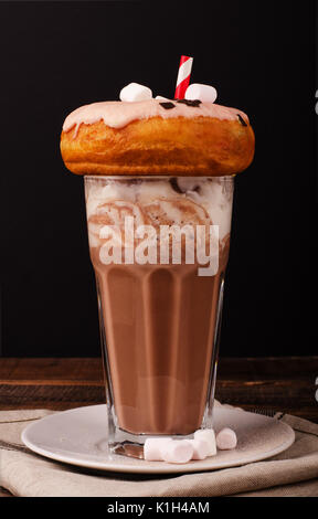 Chocolate milkshake with whipped cream and donut on a wooden background - Stock Photo