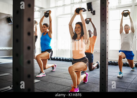Smiling young woman doing lunges with weights while working out with a diverse group of people in a gym - Stock Photo