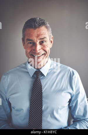 Portrait of a handsome mature businessman wearing a shirt and tie smiling and standing confidently alone in an office - Stock Photo