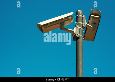 Two CCTV security cameras mounted on high post for school yard monitoring and control - Stock Photo