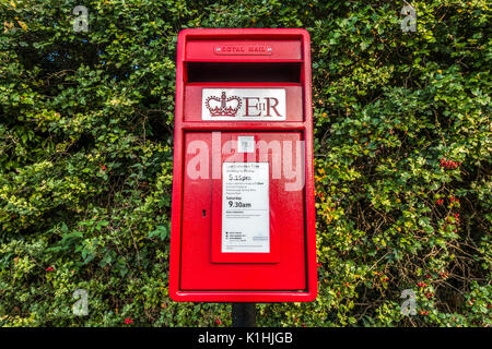 Royal Mail post box, painted bright red and displaying the pickup schedule for this local collection point within - Stock Photo