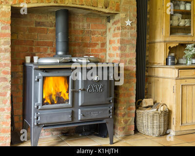 A cast iron Esse Ironheart wood burning stove, alight in a British country kitchen. - Stock Photo