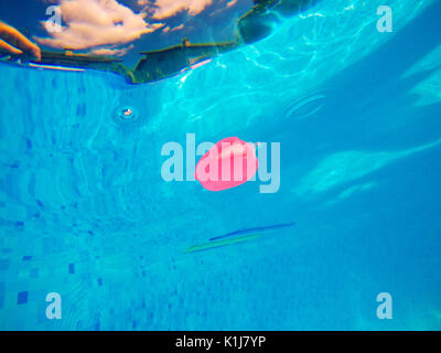 Generic rubber fish toy floating in swimming pool, summertime activity and enjoyment, underwater view - Stock Photo