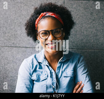 Stylishly dressed young African woman smiling while standing with her arms crossed against a wall listing to music - Stock Photo
