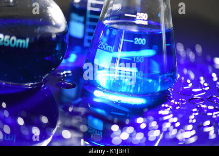 Graduated Conical Science Beakers on blue acrylic - Stock Photo