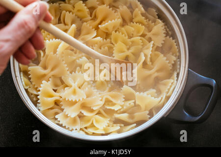 Farfalle pasta cooking in a pot - Stock Photo