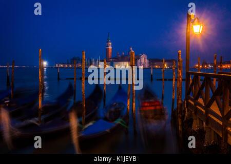 Gondolas at twilight with the island of San Giorgio Maggiore in the background. - Stock Photo