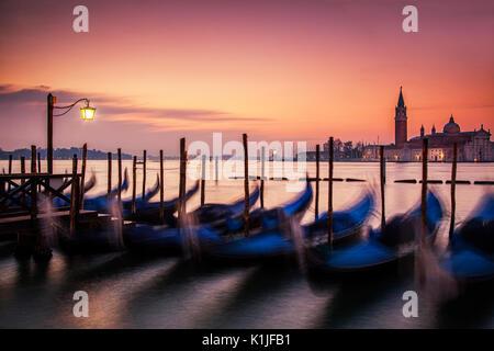 Sinrise over the gondolas of Venice, Italy and the island off San Giorgio Maggiore. - Stock Photo