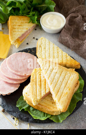 Pressed and toasted classic double sandwich with ham and cheese on a gray stone or slate background. - Stock Photo