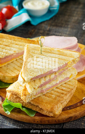 Pressed and toasted double sandwich with ham and cheese, served with lettuce leaves on a kitchen wooden table. - Stock Photo