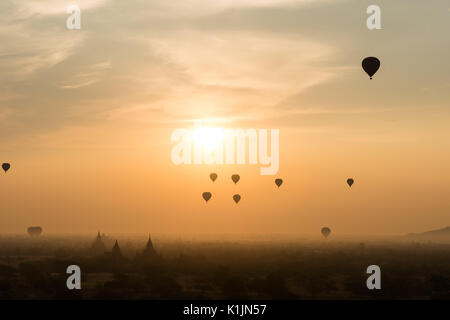 Hot air baloons flying over temples of Central Plain at sunrise, Bagan, Myanmar. - Stock Photo