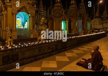 Buddhist monk prays in front of Buddha image in Shwedagon Pagoda, Yangon, Myanmar. - Stock Photo